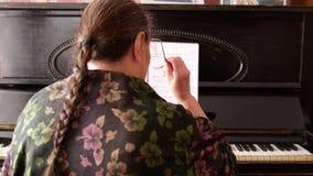 El retrato de una mujer mayor con los vidrios acerca al piano almacen de metraje de vídeo