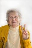 El retrato de una mujer mayor sonriente, mano muestra paz Imagen de archivo libre de regalías