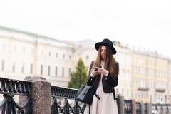 El retrato de una mujer moderna joven vistió con la lectura del estilo algo en su teléfono elegante mientras que se colocaba en l Foto de archivo