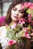 El retrato de una mujer morena hermosa en vestido rosado y coloridos componen al aire libre en jardín de la azalea Imagenes de archivo