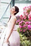 El retrato de una mujer morena hermosa en vestido rosado y coloridos componen al aire libre en jardín de la azalea Imagen de archivo libre de regalías