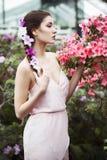 El retrato de una mujer morena hermosa en vestido rosado y coloridos componen al aire libre en jardín de la azalea Fotos de archivo