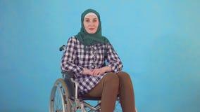 El retrato de una mujer musulmán joven inhabilitó en una silla de ruedas en un fondo azul almacen de metraje de vídeo
