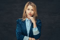 El retrato de una mujer de negocios rubia sensual se vistió en un traje formal y una camisa azul, presentando en un estudio En a foto de archivo