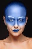 El retrato de una mujer que está presentando cubrió con la pintura azul Imágenes de archivo libres de regalías