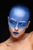 El retrato de una mujer que está presentando cubrió con la pintura azul Fotos de archivo libres de regalías