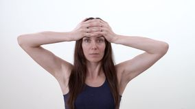 El retrato de una mujer que hace el ejercicio facial para el tratamiento de la línea de la frente arruga Aislado Fondo blanco almacen de video