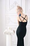 El retrato de una mujer rubia atractiva joven hermosa con maquillaje apacible en vestido negro furtivo mantuvo bien el cuerpo y l Foto de archivo libre de regalías