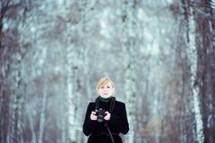 El retrato de una mujer rubia en una capa negra, con una cámara a disposición, en fondo empañó el bosque del abedul Fotografía de archivo libre de regalías