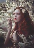 El retrato de una mujer sensual joven hermosa con el pelo rizado rojo muy largo en primavera florece Colores de la primavera fotos de archivo