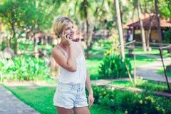 El retrato de una mujer sonriente hermosa que usa un teléfono móvil aventaja Fotografía de archivo libre de regalías