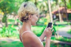 El retrato de una mujer sonriente hermosa que usa un teléfono móvil aventaja Imagen de archivo
