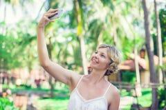 El retrato de una mujer sonriente hermosa que usa un teléfono móvil aventaja Fotos de archivo
