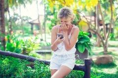 El retrato de una mujer sonriente hermosa que usa un teléfono móvil aventaja Foto de archivo libre de regalías