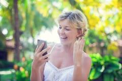 El retrato de una mujer sonriente hermosa que usa un teléfono móvil aventaja Foto de archivo