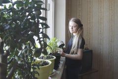 El retrato de una niña en casa que riega florece en ventana Fotos de archivo