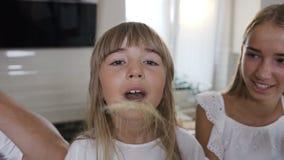 El retrato de una niña encantadora con el pelo largo hace que un bigote de maíz hojea y mira la cámara, madre almacen de video