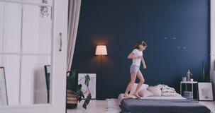 El retrato de una niña que escucha la música con los auriculares y que baila en sus padres acuesta Concepto: Música metrajes