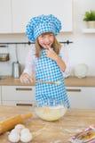 El retrato de una niña sonriente en un cocinero viste pruebas una pasta en un cuenco foto de archivo