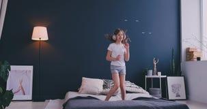 El retrato de una ni?a que escucha la m?sica con los auriculares y que baila en sus padres acuesta Concepto: M?sica metrajes
