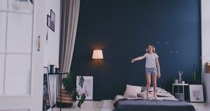 El retrato de una ni?a que escucha la m?sica con los auriculares y que baila en sus padres acuesta Concepto: M?sica almacen de metraje de vídeo