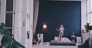 El retrato de una ni?a que escucha la m?sica con los auriculares y que baila en sus padres acuesta Concepto: M?sica almacen de video