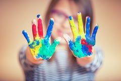 El retrato de una pequeña demostración pre-adolescente de la muchacha del estudiante pintó las manos Foto entonada fotografía de archivo libre de regalías