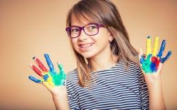 El retrato de una pequeña demostración pre-adolescente de la muchacha del estudiante pintó las manos Foto entonada fotos de archivo