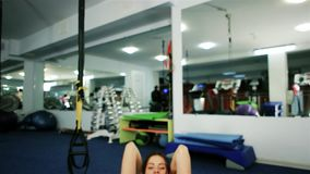 El retrato de una prensa oscilante de la mujer joven, atleta atractivo de la muchacha enganchó a ejercicios en el trabajo abdomin almacen de metraje de vídeo