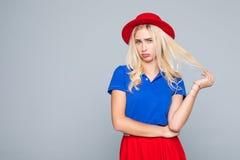 El retrato de una señora de moda imponente ofendió a la muchacha en el vestido rojo brillante que presentaba sobre fondo gris Bel Imágenes de archivo libres de regalías