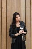 El retrato de una tenencia femenina hermosa joven se lleva el café mientras que se opone al aire libre a la pared de madera, Imagen de archivo