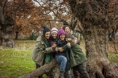 El retrato del abrazo del grupo de amigos jovenes se sienta en un tronco grande de un árbol Foto de archivo libre de regalías