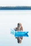El retrato del adolescente de reclinación que flota en piscina inflable azul gandulea al aire libre Fotos de archivo libres de regalías