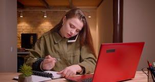 El retrato del adolescente joven que habla en el teléfono móvil mira en el ordenador portátil atento y hace notas en oficina almacen de metraje de vídeo
