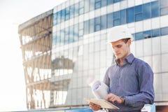 El retrato del arquitecto o del ingeniero jefe joven confiado utiliza la tableta digital en el emplazamiento de la obra foto de archivo libre de regalías