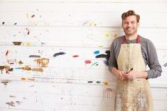 El retrato del artista de sexo masculino Leaning Against Paint cubrió la pared Fotos de archivo libres de regalías