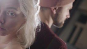 El retrato del azul joven observó a la mujer rubia que se colocaba cerca de hombre barbudo en sombrero metrajes