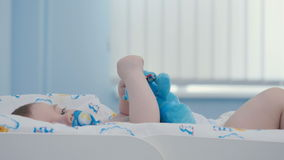 El retrato del bebé adorable chupa la entrerrosca y el juego con el juguete metrajes