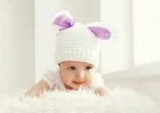 El retrato del bebé lindo en blanco hizo punto el sombrero con el conejo de los oídos Imagen de archivo libre de regalías