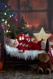 El retrato del bebé recién nacido en Papá Noel viste en pequeña cama de bebé Imagen de archivo