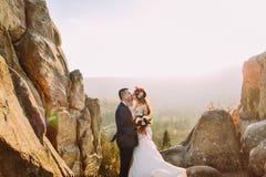 El retrato del beso romántico de los pares del recién casado en puesta del sol se enciende en paisaje asombroso de la montaña con Imagen de archivo libre de regalías