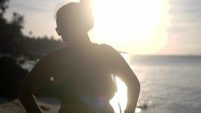 El retrato del bikini de la mujer joven y de los soportes hermosos de las gafas de sol que llevan en la playa tropical con el sol metrajes
