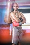El retrato del boxeador de sexo masculino confiado que se colocaba con los brazos cruzó por el saco de arena Fotos de archivo