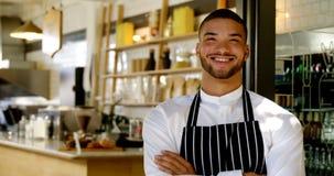 El retrato del camarero sonriente que se colocaba con los brazos cruzó 4k metrajes