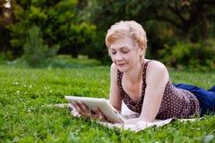 El retrato del centro envejeció a la mujer que usaba la tableta en el parque imágenes de archivo libres de regalías