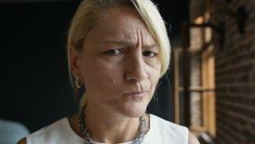 El retrato del cierre para arriba de la mujer media enojada seria de los años de la cara con el pelo rubio muestra la emoción Den metrajes