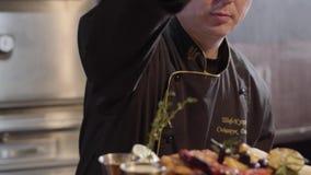 El retrato del cocinero en la porción negra de los guantes y de la sal en un escritorio asó a la parrilla pescados, cortó pedazos almacen de video