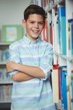 El retrato del colegial sonriente que se colocaba con los brazos cruzó en biblioteca Imagen de archivo