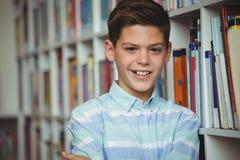 El retrato del colegial sonriente que se colocaba con los brazos cruzó en biblioteca Fotos de archivo