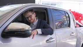 El retrato del comprador feliz del coche, hombre del cliente goza del nuevo automóvil y muestra las llaves que se sientan en cabi almacen de metraje de vídeo